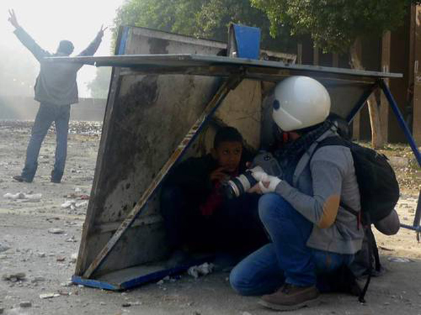 UNESCO. A. HICKSON - CC BY-NC-ND 2.0 - Periodista y chico se ponen a cubierto de las piedras lanzadas por las milicias en la azotea cerca de la plaza Tahrir, El Cairo, Egypto, en Diciembre de 2011